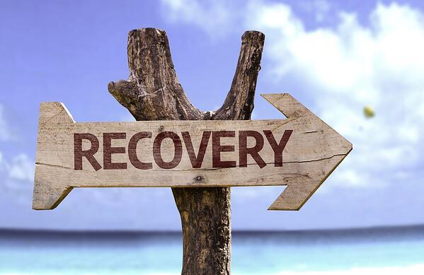 Recovery wooden sign with a beach on background